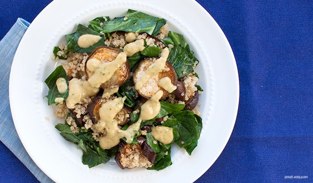 A quinoa salad with roasted eggplant and sautéed collard greens topped with a protein-packed hummus dressing.