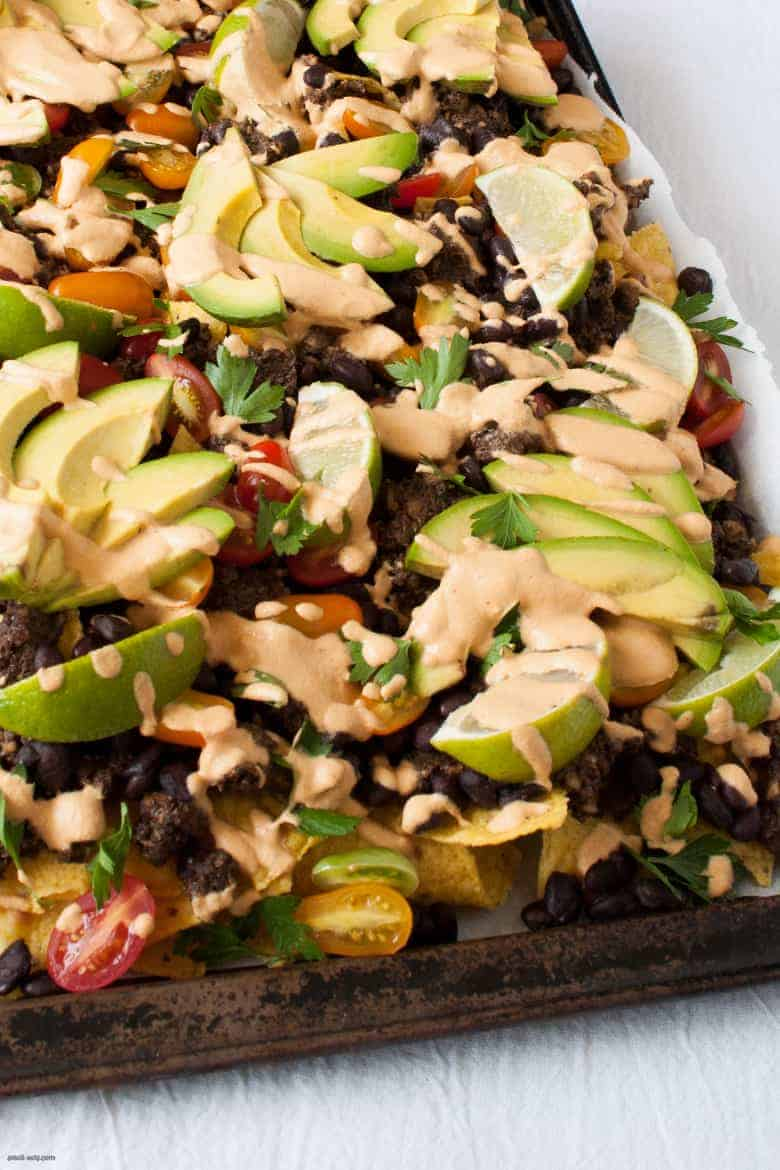 Get your nacho on with these vegan friendly nachos, topped with a cheesy vegan sauce. | Vegan Sheet Pan Nachos from small-eats.com