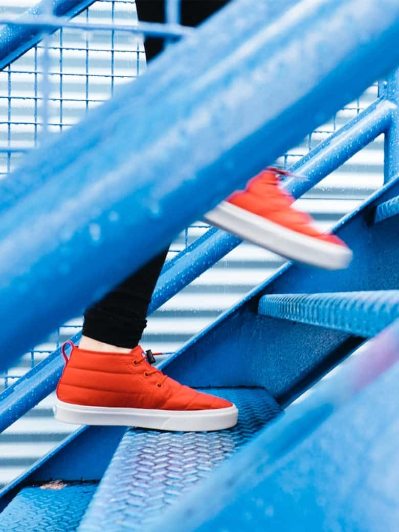 Orange sneakers walking up blue steps